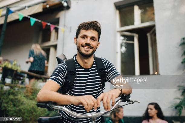 portrait of smiling young man leaning on bicycle in backyard - jonge mannen stockfoto's en -beelden