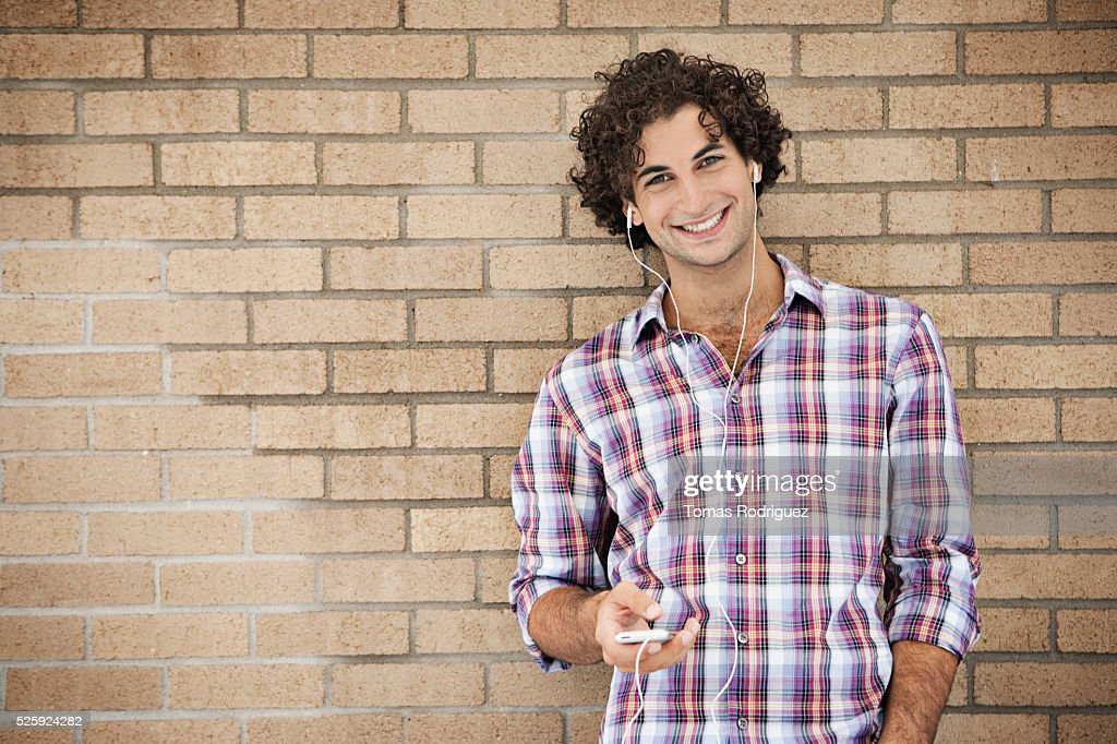 Portrait of smiling young man listening music : Stock Photo