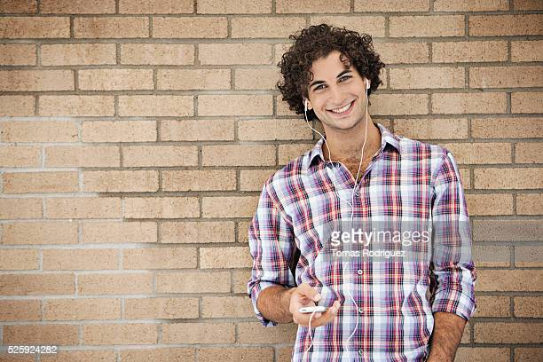 Portrait of smiling young man listening music