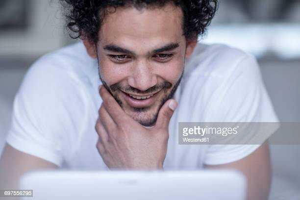 Portrait of smiling young man looking at tablet