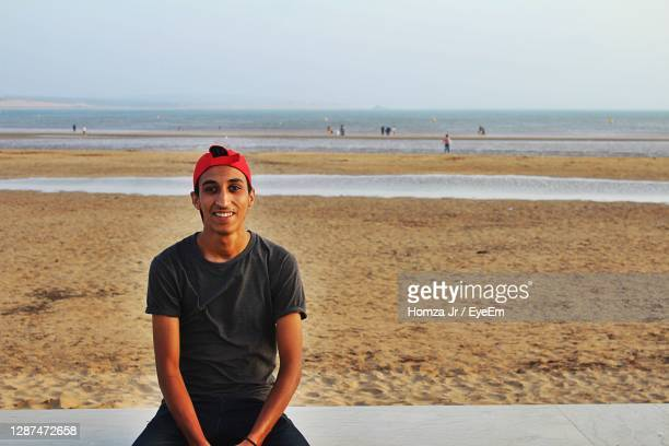 portrait of smiling young man on sitting on beach - homme maghrebin photos et images de collection