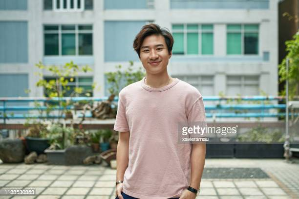 portrait of smiling young man on terrace in city - waist up stock pictures, royalty-free photos & images