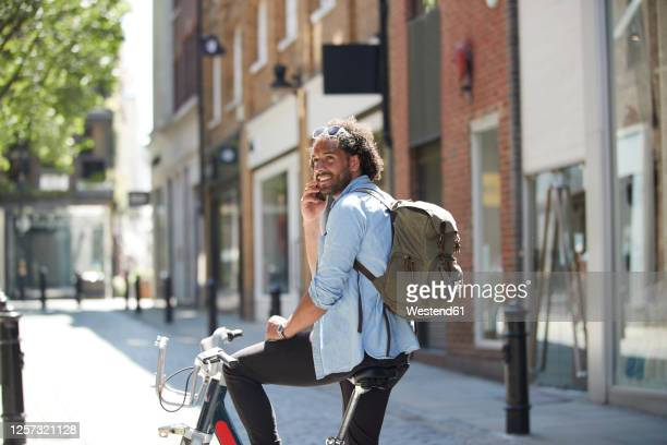 portrait of smiling young man on the phone with rental bike and backpack in the city, london, uk - mode of transport stock pictures, royalty-free photos & images