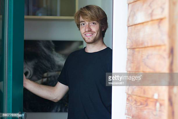 portrait of smiling young man opening entry door - in den zwanzigern stock-fotos und bilder