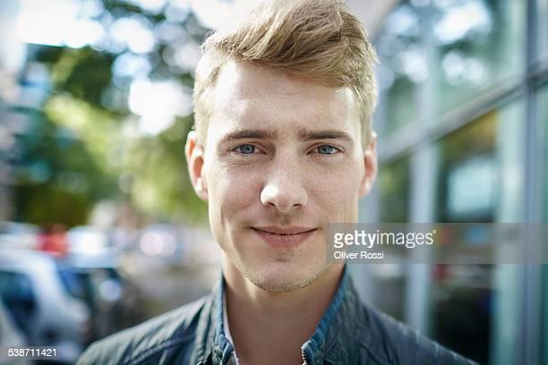 portrait of smiling young man outdoors - blondes haar stock-fotos und bilder