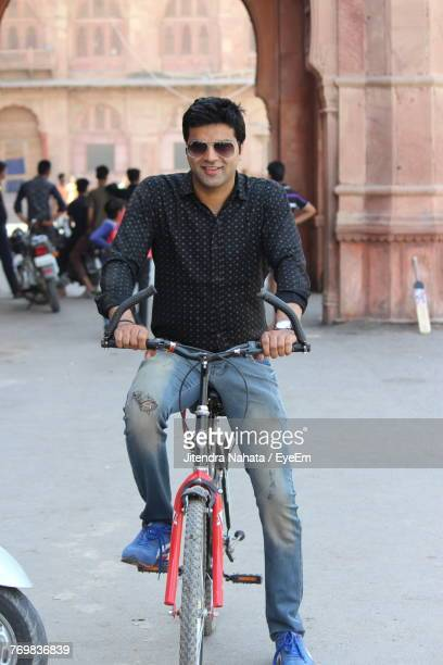 Portrait Of Smiling Young Man Riding Bicycle In City