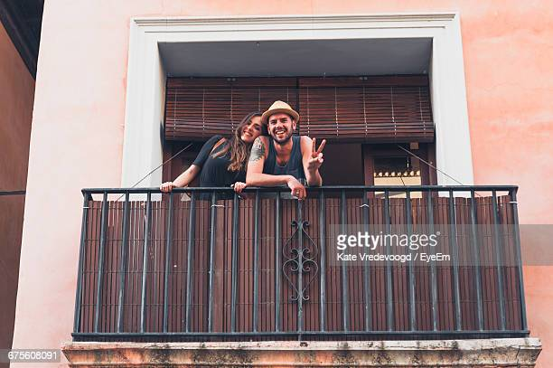 portrait of smiling young man showing peace sign by girlfriend at balcony - balcony stock pictures, royalty-free photos & images