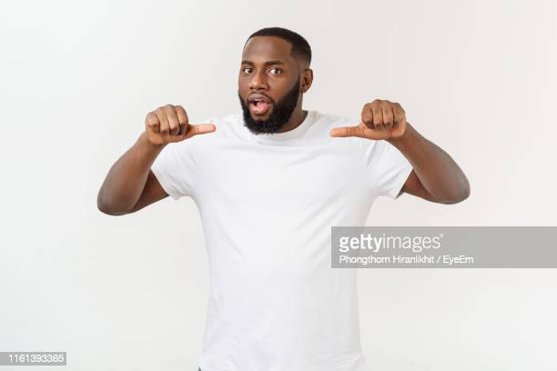 portrait of smiling young man showing thumbs up while standing against white background - t shirt photos et images de collection