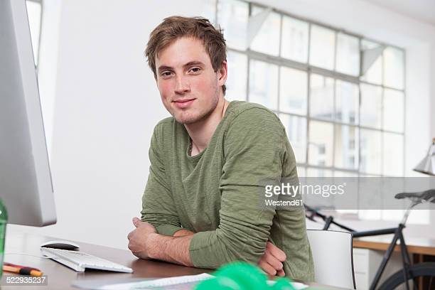 portrait of smiling young man sitting at his desk in the office - alleen één jonge man stockfoto's en -beelden