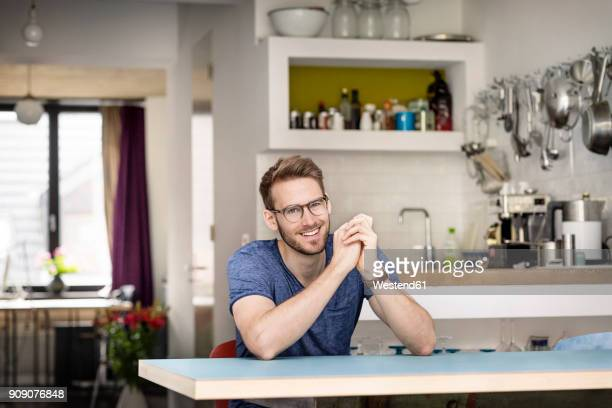 portrait of smiling young man sitting at kitchen table at home - junge männer stock-fotos und bilder