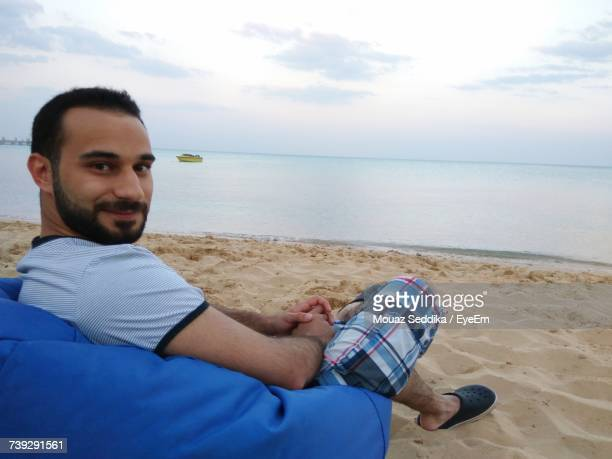 Portrait Of Smiling Young Man Sitting On Bean Bag At Beach Against Sky