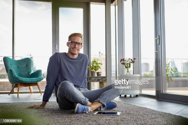portrait of smiling young man sitting on carpet with tablet at home - sitting on ground stock pictures, royalty-free photos & images
