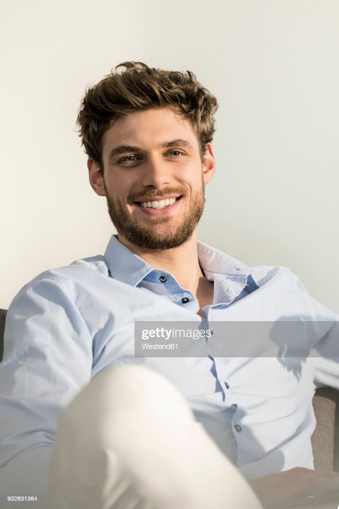 Portrait of smiling young man sitting on couch : Foto de stock