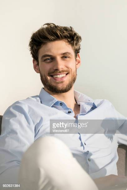 portrait of smiling young man sitting on couch - facial hair stock pictures, royalty-free photos & images