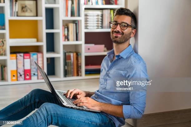 portrait of smiling young man sitting on the floor at home using laptop - solo un uomo giovane foto e immagini stock