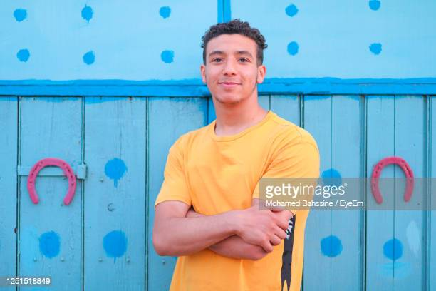 portrait of smiling young man standing against blue wall - homme maghrebin photos et images de collection