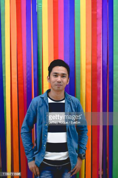 portrait of smiling young man standing against colorful ribbons - jeffrey roque stock photos and pictures