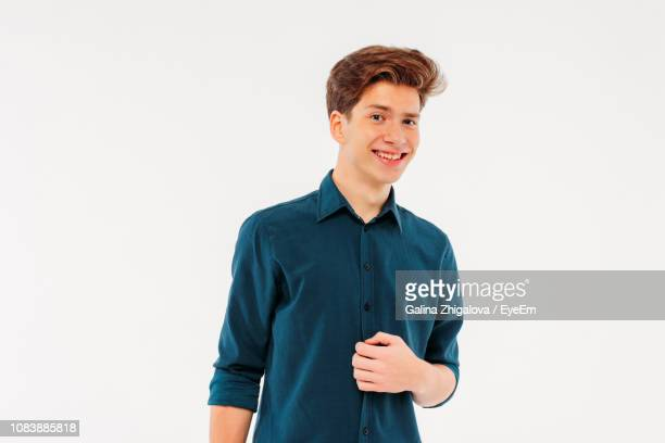 portrait of smiling young man standing against white background - 18 19 years stock pictures, royalty-free photos & images