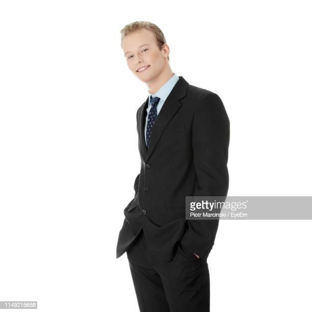 portrait of smiling young man standing against white background - ポケットに手を入れている ストックフォトと画像