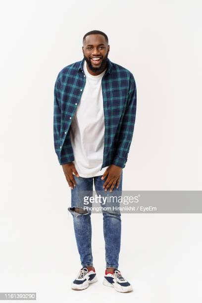 portrait of smiling young man standing against white background - black trousers stock pictures, royalty-free photos & images