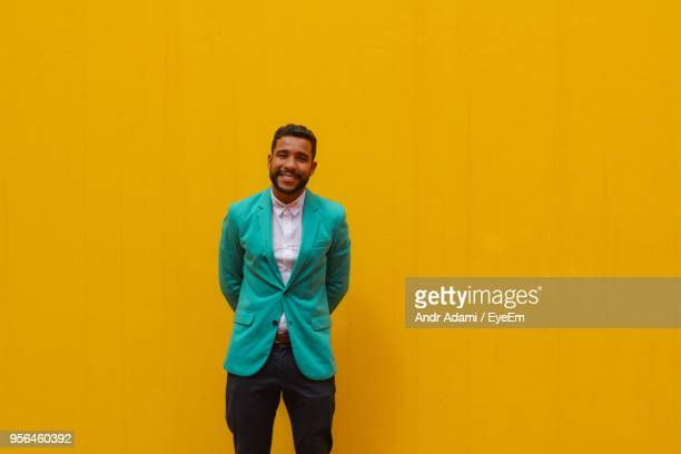 portrait of smiling young man standing against yellow wall - yellow blazer stock photos and pictures
