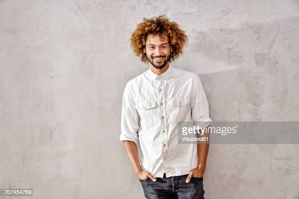 Portrait of smiling young man standing at grey wall