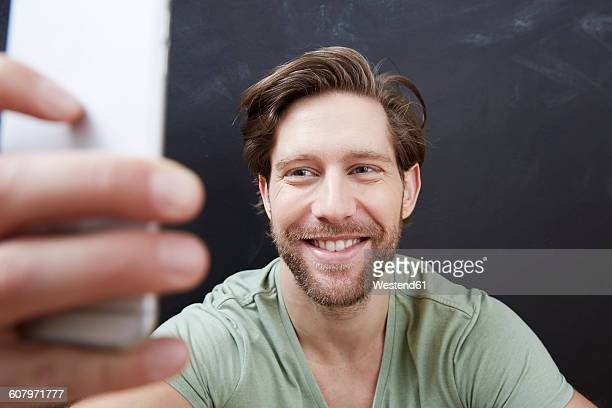 Portrait of smiling young man taking a selfie with smartphone