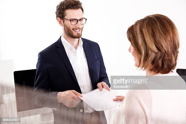 Portrait of smiling young man taking document from his colleague