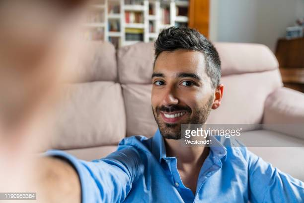 portrait of smiling young man taking selfie at home - selfie stock pictures, royalty-free photos & images