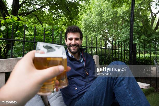 portrait of smiling young man toasting with glass of beer in garden - men friends beer outside stock pictures, royalty-free photos & images