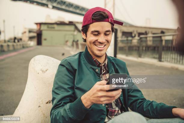portrait of smiling young man using cell phone - junge männer stock-fotos und bilder
