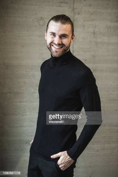 portrait of smiling young man wearing black turtleneck jumper - turtleneck stock pictures, royalty-free photos & images