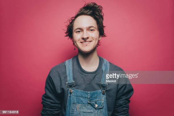 portrait of smiling young man wearing denim overalls over pink background - androgyn stock-fotos und bilder