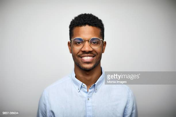 portrait of smiling young man wearing eyeglasses - occhiali da vista foto e immagini stock