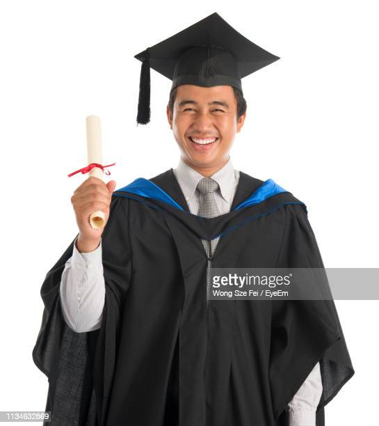 portrait of smiling young man wearing graduation gown while standing against white background - graduation background stock pictures, royalty-free photos & images