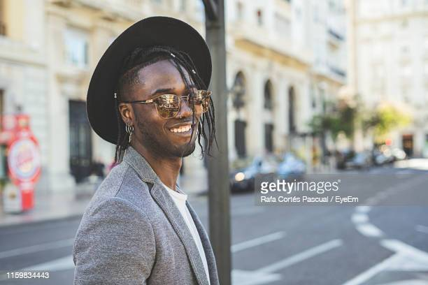 portrait of smiling young man wearing hat while standing on street - veste noire photos et images de collection