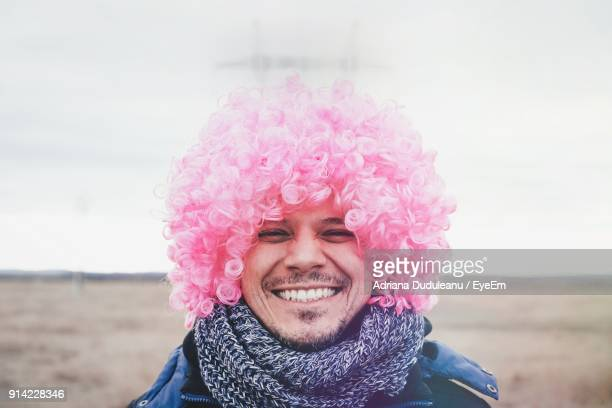Portrait Of Smiling Young Man Wearing Pink Wig Against Pink Sky