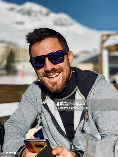 portrait of smiling young man wearing sunglasses - carnet stock photos and pictures
