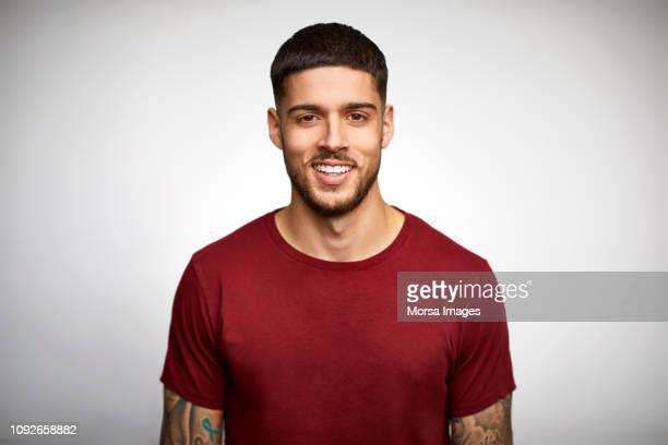 portrait of smiling young man wearing t-shirt - jonge mannen stockfoto's en -beelden