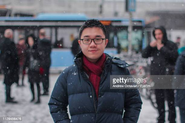 portrait of smiling young man wearing warm clothing in city during snowfall - 後ろボケ ストックフォトと画像