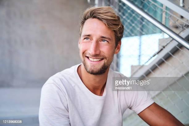 portrait of smiling young man wearing white t-shirt - solo un uomo giovane foto e immagini stock