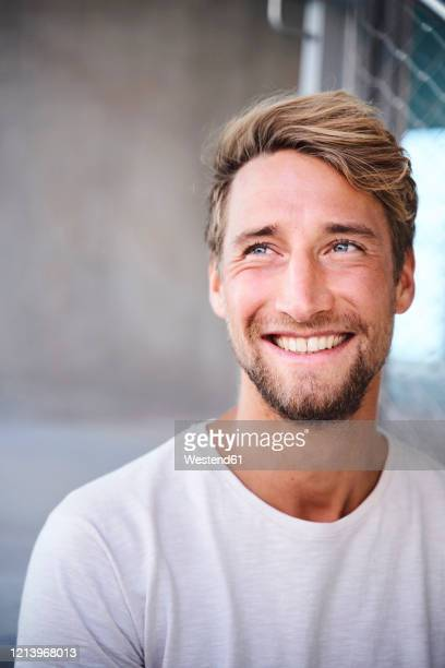 portrait of smiling young man wearing white t-shirt - facial hair stock pictures, royalty-free photos & images