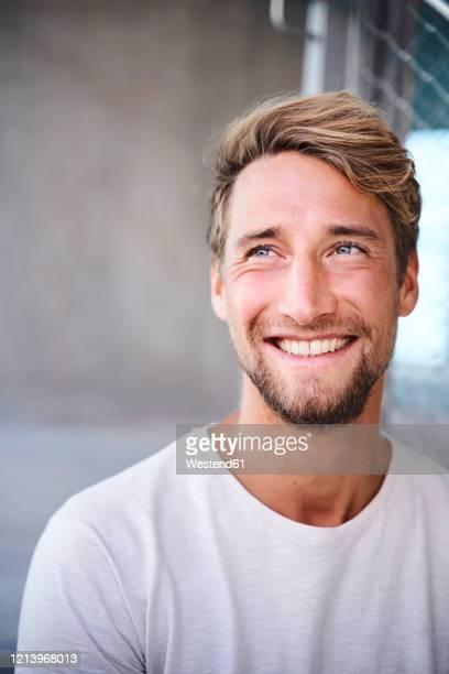 portrait of smiling young man wearing white t-shirt - barba peluria del viso foto e immagini stock