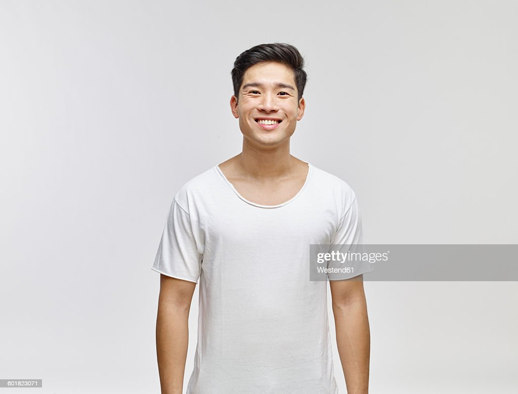 Portrait of smiling young man wearing white t-shirt : Stock Photo