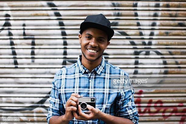 Portrait of smiling young man with baseball cap and camera in front of roller shutter