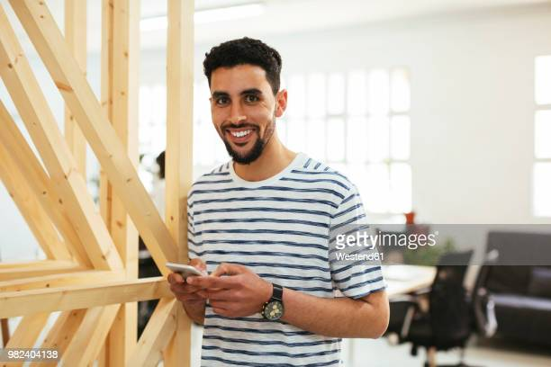 portrait of smiling young man with cell phone in office - north african ethnicity stock pictures, royalty-free photos & images