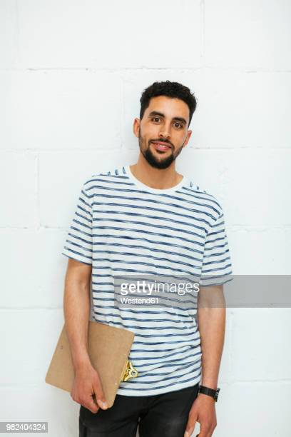 portrait of smiling young man with clipboard at brick wall - north african ethnicity stock pictures, royalty-free photos & images