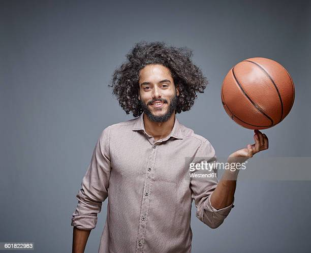 Portrait of smiling young man with curly brown hair balancing a basketball on his finger