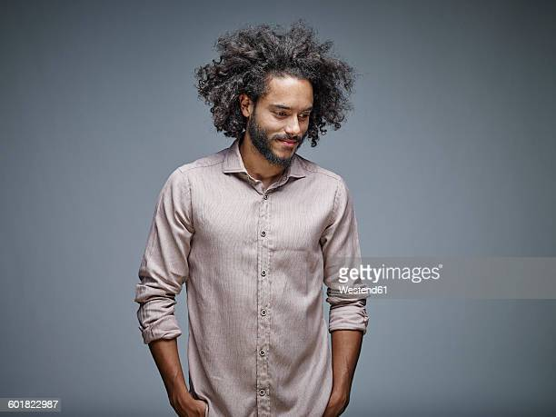 portrait of smiling young man with curly brown hair in front of grey background - waist up stock pictures, royalty-free photos & images