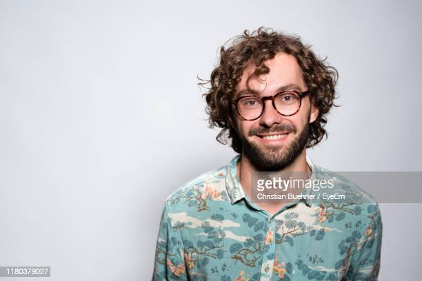 portrait of smiling young man with curly hair standing against white background - curly stock pictures, royalty-free photos & images